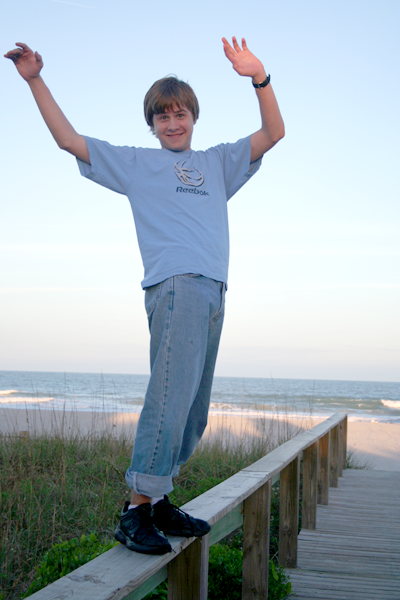 Joey balancing on boardwalk fence railing at the beach